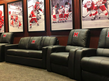 """Since the dedication of the Steve """"Coach"""" Cady Arena at the Goggin Ice Center in 2006, Miami University Ice Hockey has completed renovations within the Weight and Conditioning Room, Champions Room and Legacy Hallway. This new facility that opened in 2014 has been a celebration of the program's history and key tool in recruiting. Their players lounge, while modern and new, was need of new and additional seating. Looking for something durable, that could withstand years of use while delivering comfort and honoring their brand, they turned to DreamSeat for a tailored solution."""